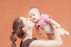 Happy mother kissing her baby at wall background Royalty Free Stock Image