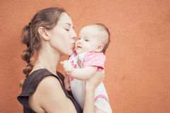 Happy mother kissing her baby at wall background Royalty Free Stock Photography
