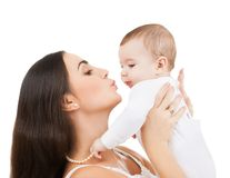 Happy mother kissing her child. Family and motherhood - happy mother kissing her child Stock Image