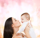 Happy mother kissing her child. Family, children, parenthood and happiness concept - happy mother kissing her child royalty free stock image