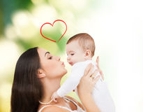 Happy mother kissing her child. Family, children, parenthood and happiness concept - happy mother kissing her child royalty free stock images