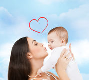 Happy mother kissing her child. Family, children, parenthood and happiness concept - happy mother kissing her child Royalty Free Stock Photos