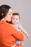 Happy mother kissing her daughter. Portrait of mother and baby at the hands of six mothers royalty free stock photos