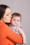 Happy mother kissing her daughter six-month. Portrait of mother and baby at the hands of six mothers stock image