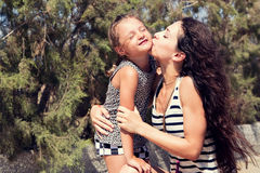 Happy mother kissing her fun enjoying daughter on summer geen ba Royalty Free Stock Photography