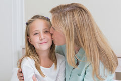 Happy mother kissing her little girl Stock Photos