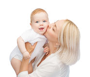 Happy mother kissing smiling baby Stock Photography