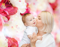 Happy mother kissing smiling baby Stock Photos