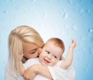 Happy mother kissing smiling baby Royalty Free Stock Images