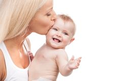 Happy mother kissing smiling infant. Blond mom and baby on white background Stock Photo