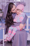 Happy mother kissing a young daughter sitting on a winter bench Royalty Free Stock Images