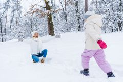 happy mother kneeling with open arms and little daughter walking in snow stock images