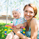 Happy mother with laughing baby sits on swing Stock Photos