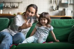 Happy mother laughing taking selfie with little daughter on smar Stock Image