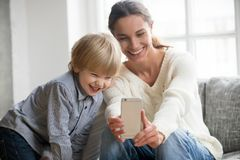 Happy mother laughing taking selfie with little son on smartphon. E at home, smiling single mom and cute adopted boy playing making photo posing for self Royalty Free Stock Photos