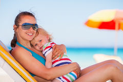 Happy mother laying on sun bed and hugging baby. Happy young mother laying on sun bed and hugging baby girl Royalty Free Stock Photos