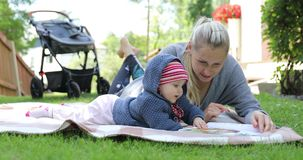 Happy mother and little baby girl reading book together on blanket stock footage
