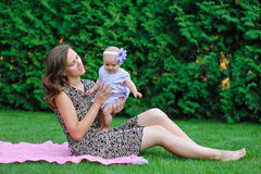 Happy mother and little baby girl resting in the summer garden Royalty Free Stock Photos