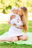 Happy mother with little baby sitting on blanket Royalty Free Stock Photo