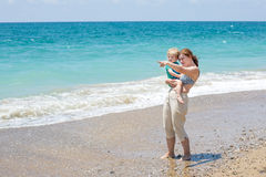 Happy mother and little baby son having fun at beach vacation Stock Photos