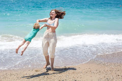 Happy mother and little baby son having fun at beach vacation Stock Images