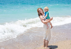Happy mother and little baby son having fun at beach vacation Royalty Free Stock Images