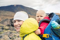 Happy mother with little boy travelling in backpack Royalty Free Stock Images