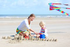 Happy mother and little child playing on the beach Royalty Free Stock Images