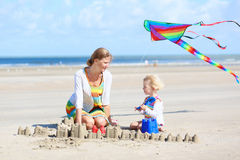 Happy mother and little child playing on the beach Stock Photos