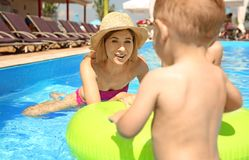 Happy mother with little child in swimming pool. Outdoors royalty free stock photo