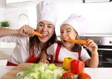 Happy mother and little daughter in apron and cook hat eating carrots together having fun at home kitchen Stock Photos