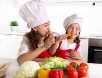 Happy mother and little daughter in apron and cook hat eating carrots together having fun at home kitchen Royalty Free Stock Photography
