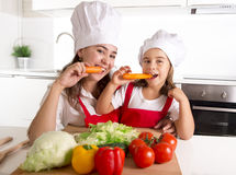 Happy mother and little daughter in apron and cook hat eating carrots together having fun at home kitchen Royalty Free Stock Photos