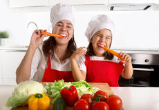 Happy mother and little daughter in apron and cook hat eating carrots together having fun at home kitchen Stock Images