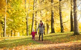 Happy mother and little daughter at autumn park royalty free stock image