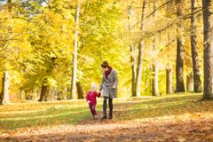 Happy mother and little daughter at autumn park royalty free stock photo