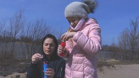 Happy mother and little daughter blowing soap bubbles stock footage