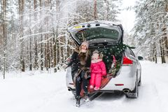 Happy mother with the little daughter and Christmas tree sitting in the car in the winter forest.  royalty free stock images