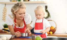 Happy mother and little daughter cooking in kitchen. Spending time all together, family fun concept.  royalty free stock image