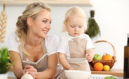 Happy mother and little daughter cooking in kitchen. Spending time all together, family fun concept.  royalty free stock images