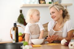 Happy mother and little daughter cooking in kitchen. Spending time all together, family fun concept.  royalty free stock photo