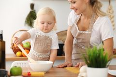 Happy mother and little daughter cooking in kitchen. Spending time all together, family fun concept.  royalty free stock photography
