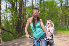 Happy mother and little daughter cycling bicycle at the park Stock Photos