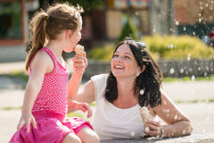 Happy mother and little daughter eating ice-cream in summer day Stock Image