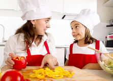 Happy mother and little daughter at home kitchen preparing paprika salad in apron and cook hat Royalty Free Stock Photo