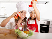 Happy mother and little daughter at home kitchen preparing paprika salad in apron and cook hat Stock Photography