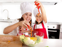 Happy mother and little daughter at home kitchen preparing paprika salad in apron and cook hat Stock Image