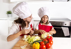 Happy mother and little daughter at home kitchen preparing salad in apron and cook hat Stock Photo
