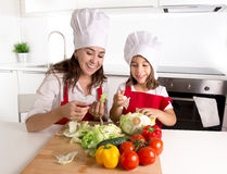 Happy mother and little daughter at home kitchen preparing salad in apron and cook hat Royalty Free Stock Images