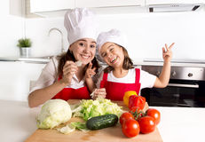 Happy mother and little daughter at home kitchen preparing salad in apron and cook hat Royalty Free Stock Image